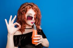 太阳镜的一个美丽的女孩喝自然健康的汁液、概念和生活方式,展示与她的一个好姿态 免版税库存图片