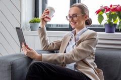 太阳镜的一名妇女与片剂个人计算机一起使用 免版税图库摄影
