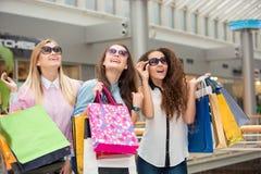 太阳镜的三个美丽的女孩有购物的 库存图片
