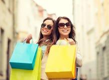 太阳镜的两个女孩有在ctiy的购物袋的 免版税库存图片