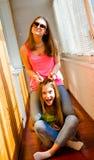 太阳镜的两个滑稽的相当十几岁的女孩 免版税库存图片