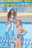 太阳镜的二个美丽的女孩在一个空的池 免版税图库摄影