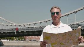 太阳镜的人看在一座大桥的背景的纸地图 股票录像