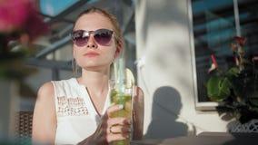 太阳镜的企业夫人在夏天喝着与秸杆的鸡尾酒在咖啡馆 股票录像