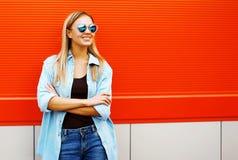 太阳镜的俏丽的微笑的妇女在都市样式 免版税库存照片