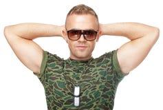 太阳镜的军队战士用在他的头后的手 免版税库存照片