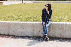 太阳镜的可爱的女孩在草在公园 免版税库存图片