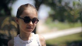 太阳镜的可爱的女孩微笑和笑本质上的 股票录像