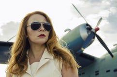 太阳镜的可爱的妇女在近的军用飞机之外 免版税库存照片