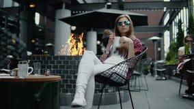 太阳镜的可爱的少妇喝在城市街道咖啡馆的茶 股票视频