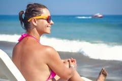 太阳镜的可爱的少妇在海海滩 海滩的女孩晒日光浴反对蓝色海的在一个清楚的晴天 免版税图库摄影