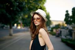 太阳镜的和一个白色帽子的走在城市的年轻美丽的妇女 库存照片