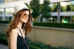 太阳镜的和一个白色帽子的走外面在城市的年轻美丽的妇女 库存照片