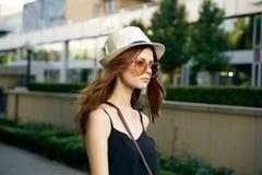 太阳镜的和一个白色帽子的走沿街道的年轻美丽的妇女在城市 免版税库存图片