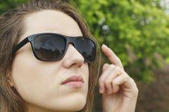太阳镜的女孩下雨看天空 免版税库存图片