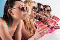 太阳镜的女孩喝鸡尾酒的,当晒日光浴在游泳的床垫时 免版税库存照片