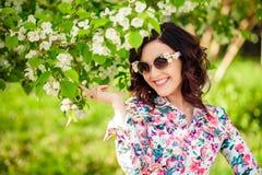 太阳镜的女孩在一棵开花的苹果树 免版税库存图片