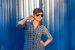 太阳镜的女孩在蓝色背景的衬衣 免版税库存照片