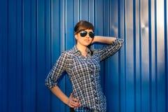 太阳镜的女孩在蓝色背景的衬衣 图库摄影