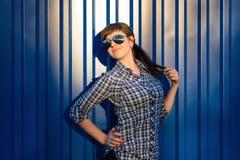 太阳镜的女孩在蓝色背景的衬衣 库存图片