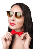 太阳镜的女孩浅黑肤色的男人调直他的蝶形领结红色 库存照片