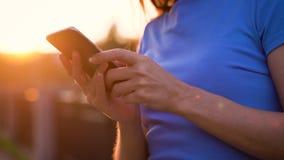太阳镜的妇女使用户外智能手机在日落 股票录像