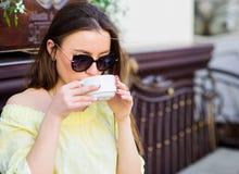 太阳镜的妇女喝咖啡户外 女孩在咖啡馆热奶咖啡杯子放松 咖啡因药量 精力充沛的咖啡 免版税库存图片