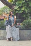 太阳镜的妇女有时尚snakeskin坐Python的袋子的外面 可视巴厘岛美丽的印度尼西亚海岛kuta人连续形状日落的城镇 免版税库存图片