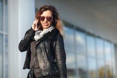 太阳镜的妇女黑皮夹克,有购物袋的黑牛仔裤谈话在被反映的窗口o前面的手机 库存照片