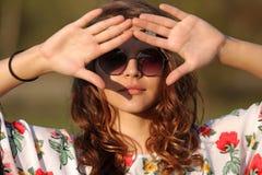 太阳镜的嬉皮女孩盖她的从太阳手的面孔户外 库存图片