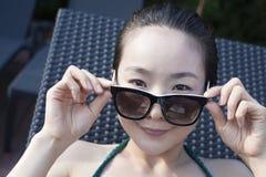 太阳镜的少妇和拿着太阳镜和看照相机的泳装 免版税库存照片