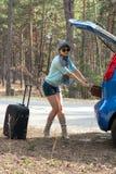太阳镜的少妇在带着手提箱的汽车附近 免版税图库摄影