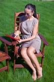 太阳镜的少妇在椅子室外看 免版税库存图片