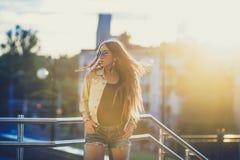 太阳镜的少妇在背景中获得与室外的乐趣,日落 免版税库存照片