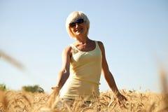 太阳镜的少妇在麦田 免版税图库摄影