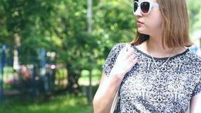 太阳镜的少妇,步行在公园 影视素材