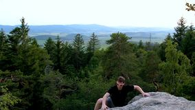 太阳镜的年轻人在捷克风景的石岩石上升 股票视频