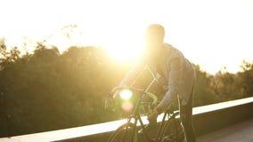 太阳镜的年轻人坐他的自行车和乘坐的自行车在空的自行车路通过绿色树公园在晴朗的夏天 影视素材