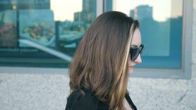 太阳镜的年轻女商人走在城市街道的在办公楼附近 可爱的女实业家档案  股票录像