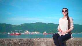 太阳镜的年轻怀孕的迷人的女孩在晴天在夏天 女孩坐堤防在海附近 股票视频