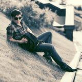 太阳镜的年轻时尚人坐草在城市公园 库存图片