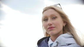 太阳镜的年轻美女 步行的俏丽的金发碧眼的女人 t 股票录像