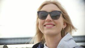 太阳镜的年轻美女 步行的俏丽的金发碧眼的女人 t 股票视频