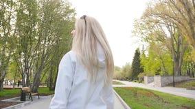 太阳镜的年轻美女 步行的俏丽的金发碧眼的女人 t 影视素材