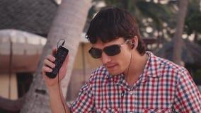 太阳镜的年轻英俊的时髦的人在热带海滩听到音乐并且跳舞在日落时间 慢的行动 股票录像