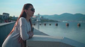 太阳镜的年轻迷人的女孩在清楚的夏天天气 女孩在堤防站立在海附近 股票录像