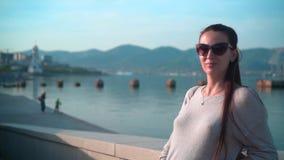 太阳镜的年轻迷人的女孩在清楚的夏天天气 女孩在堤防站立在海附近 影视素材