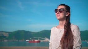 太阳镜的年轻迷人的女孩在清楚的夏天天气 女孩坐堤防在海附近 股票视频
