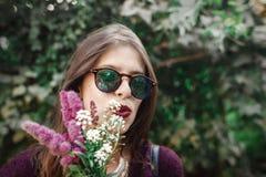 太阳镜的微笑与野花花束的愉快的boho女孩画象在晴朗的庭院里 时髦的行家无忧无虑的女孩 免版税图库摄影
