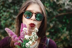 太阳镜的微笑与野花花束的愉快的boho女孩画象在晴朗的庭院里 时髦的行家无忧无虑的女孩 免版税库存图片